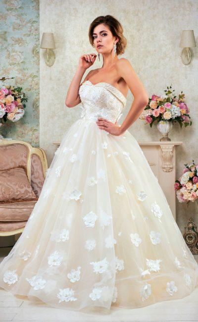 Роскошное свадебное платье в кремовых тонах, украшенное по подолу объемными бутонами.