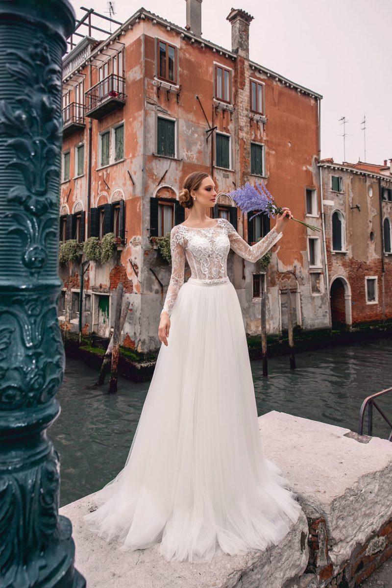 Сдержанное свадебное платье с великолепным шлейфом и длинным кружевным рукавом.