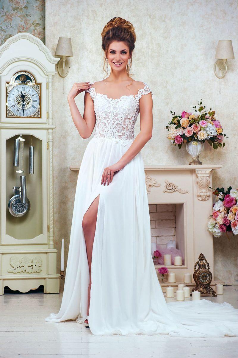 Утонченное свадебное платье с кружевным верхом и высоким разрезом на юбке со шлейфом.