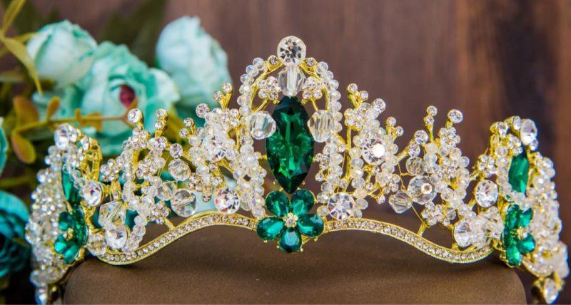 Золотистая свадебная диадема, украшенная кристаллами и зелеными камнями.