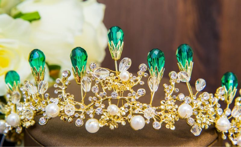 Золотистая свадебная диадема, оригинально оформленная зелеными кристаллами.