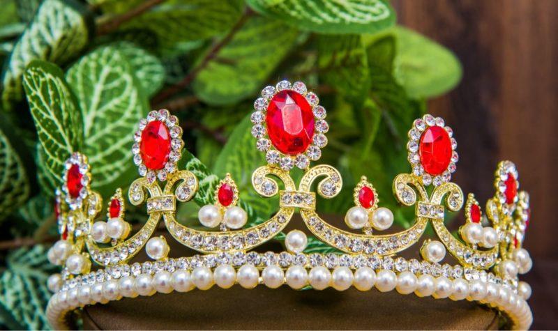 Стильная золотистая корона для невесты, украшенная жемчугом и красными кристаллами.