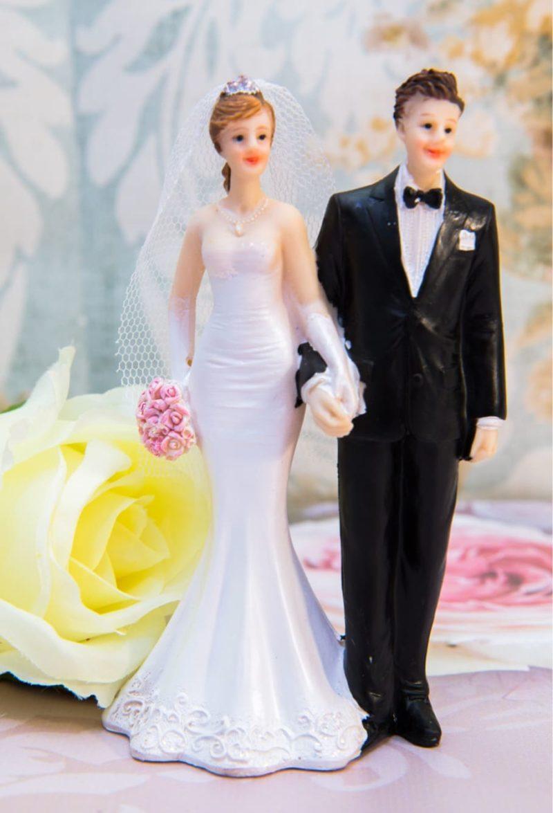 Изысканная фигурка для торта с невестой в белом платье и женихом в черном костюме.