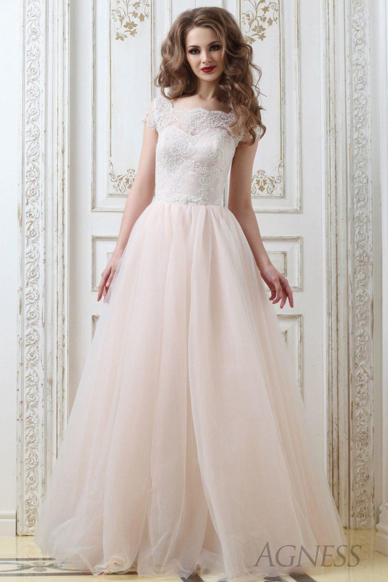 Пышное свадебное платье с кружевным верхом и многослойной кремовой юбкой.