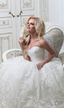 Открытое свадебное платье с лифом в форме сердца и юбкой, покрытой кружевом.