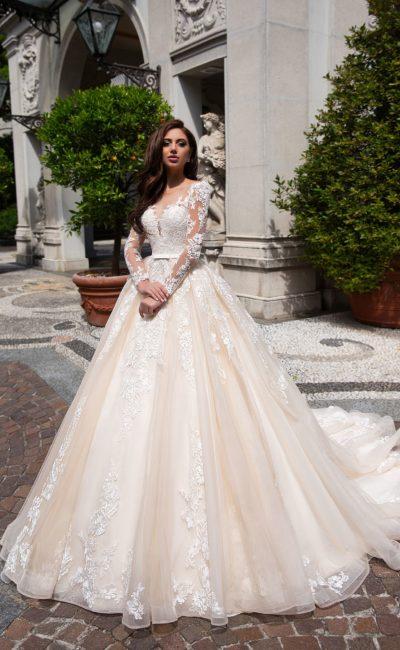 Персиковое свадебное платье пышного кроя с длинным прозрачным рукавом.