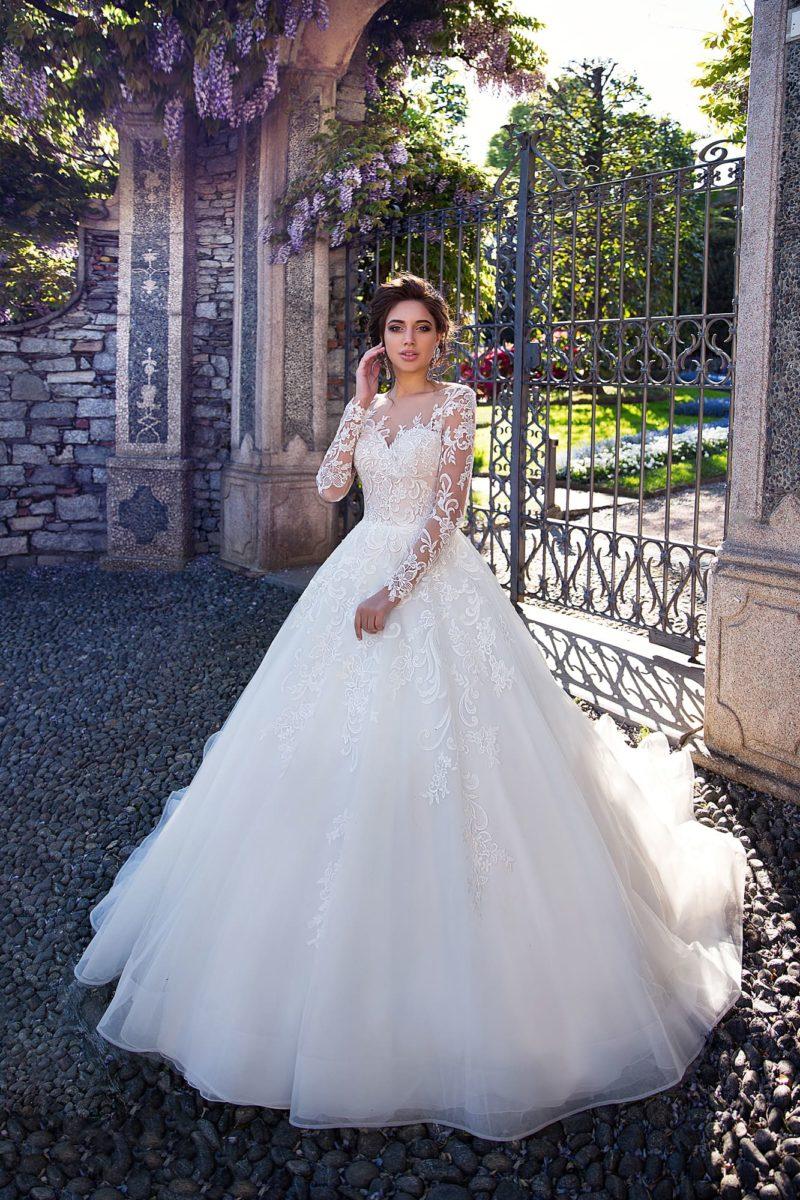 Пышное свадебное платье с выразительной кружевной отделкой и тонким длинным рукавом.