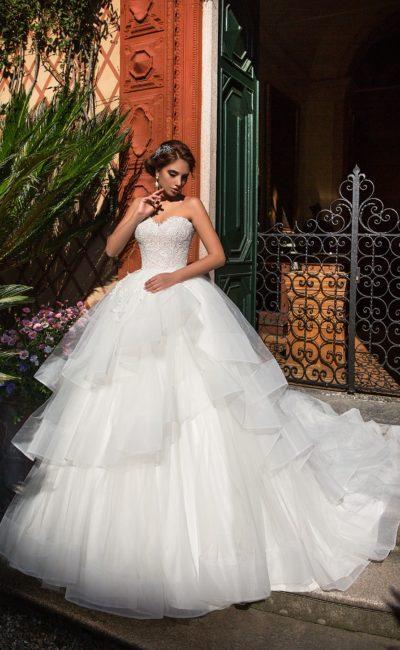 Открытое свадебное платье пышного кроя с чарующей многоярусной юбкой со шлейфом.