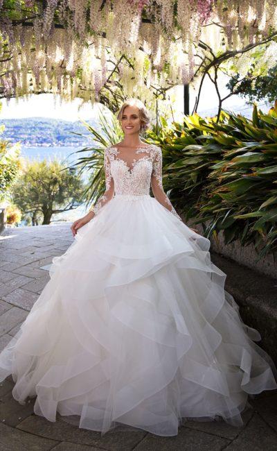 Фантазийное свадебное платье с длинным кружевным рукавом и пышной многоярусной юбкой.