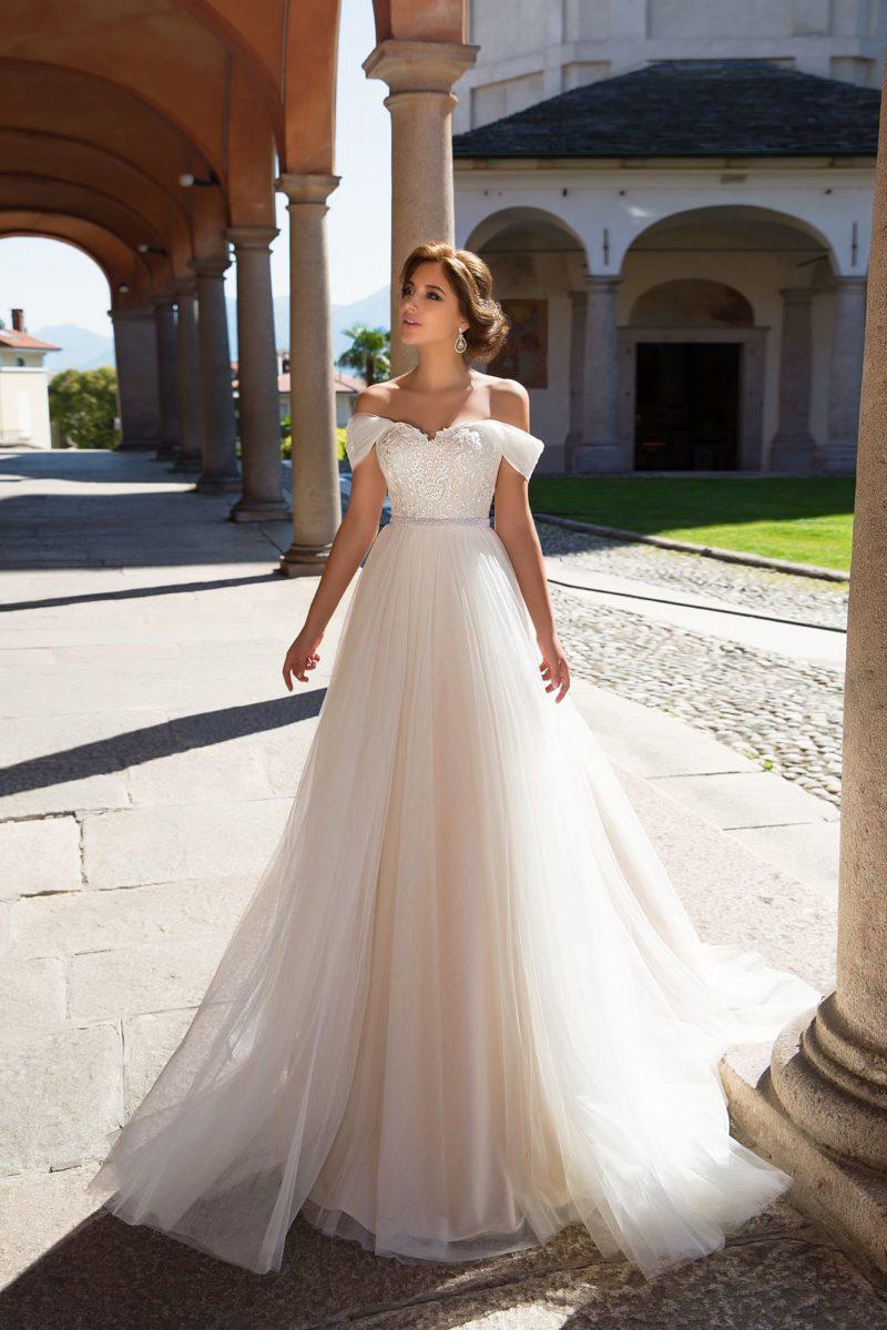 Великолепное свадебное платье с завышенной талией и бретелями на предплечьях.