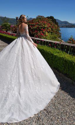 Пышное свадебное платье с длинным рукавом и элегантным портретным декольте.