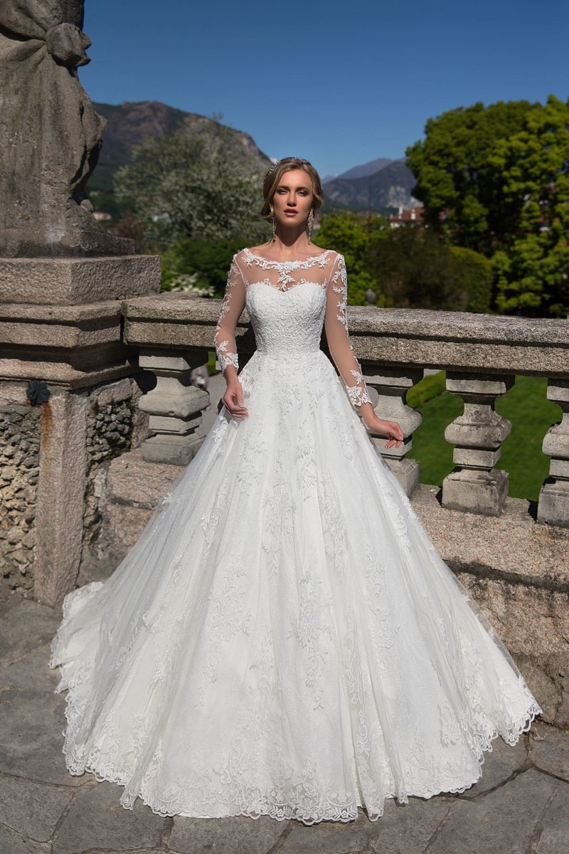 Романтичное кружевное свадебное платье с прозрачным рукавом и юбкой А-силуэта.