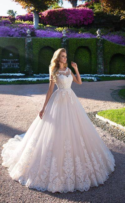 Кружевное свадебное платье с фигурным вырезом вокруг шеи и элегантным шлейфом.