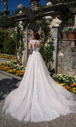 Свадебное платье с юбкой А-силуэта сложного кроя и элегантным верхом с коротким рукавом.