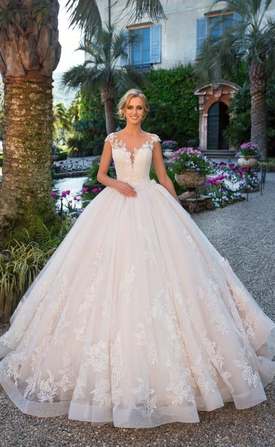 Пышное свадебное платье с крупной цветочной отделкой и эффектным вырезом на лифе.