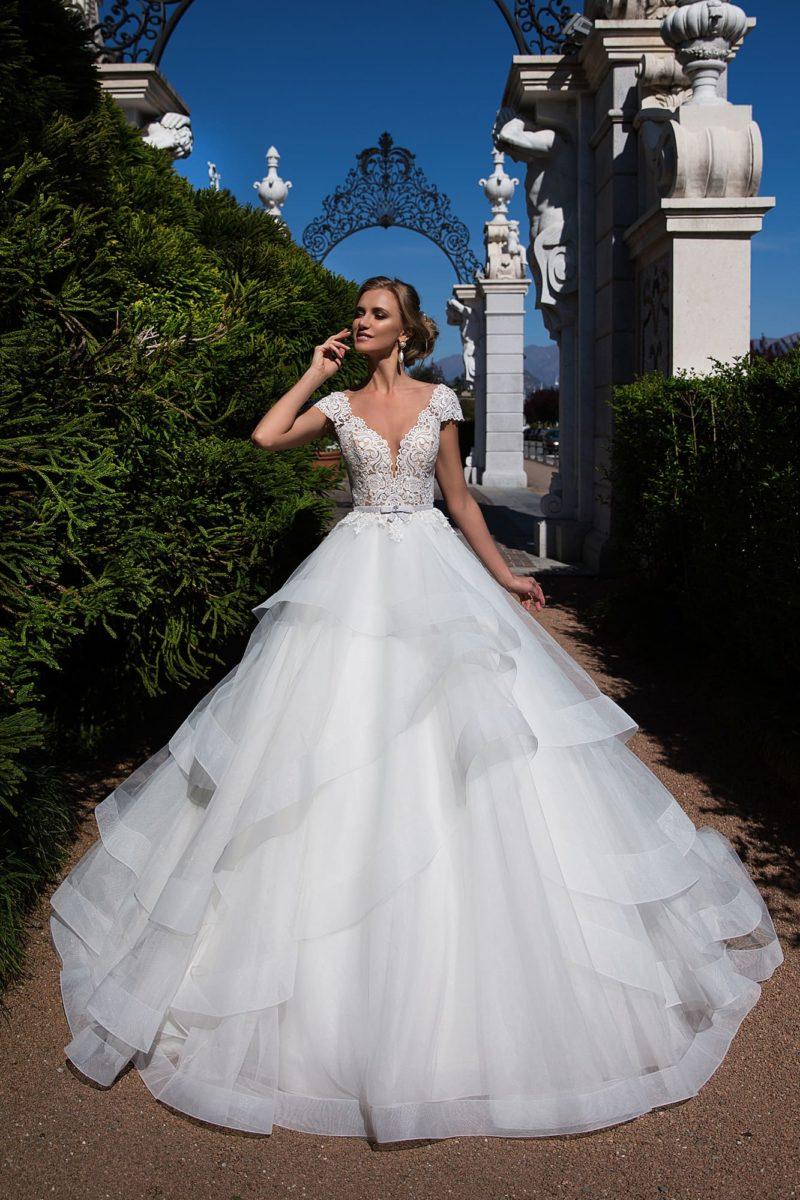 Очаровательное свадебное платье с полупрозрачным кружевным верхом и коротким рукавом.