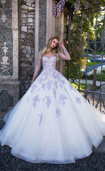Пышное свадебное платье с длинным рукавом, украшенное фиолетовыми аппликациями.