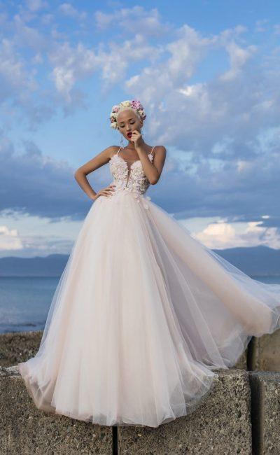 Свадебное платье в кремовых тонах, с открытым верхом и пышной юбкой со шлейфом.