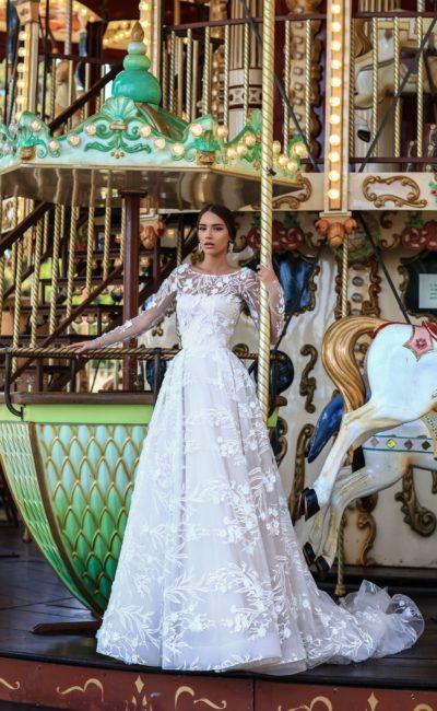 Пышное свадебное платье с крупным цветочным узором отделки и длинным рукавом.