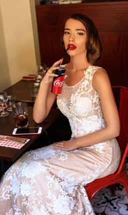 Бежевое свадебное платье «принцесса» с закрытым лифом и белой кружевной отделкой.