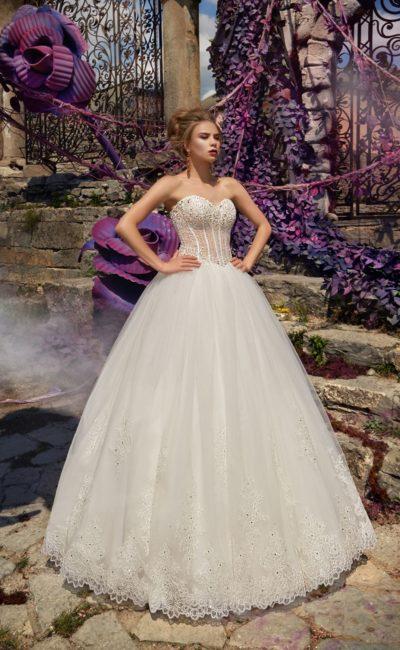 Пышное свадебное платье с белой юбкой и кремовым корсетом, украшенным бисером.