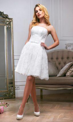 Короткое свадебное платье с открытым лифом из атласа и кружевной юбкой до колена.