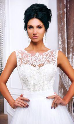 Пышное свадебное платье с закрытым лифом, оформленным полупрозрачной тканью.
