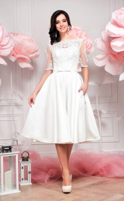 Закрытое свадебное платье с кокетливой атласной юбкой А-силуэта длиной до колена.