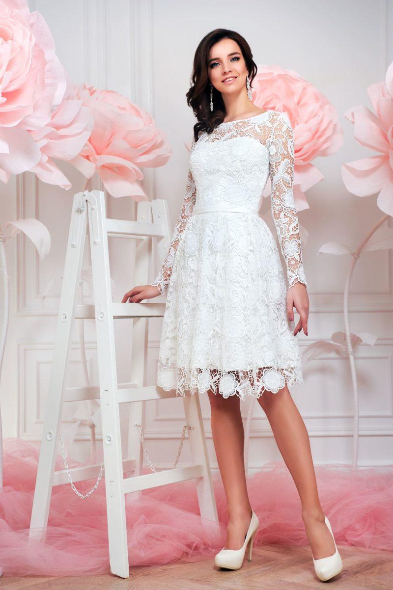 Кружевное свадебное платье с длинным рукавом и юбкой А-силуэта длиной до колена.