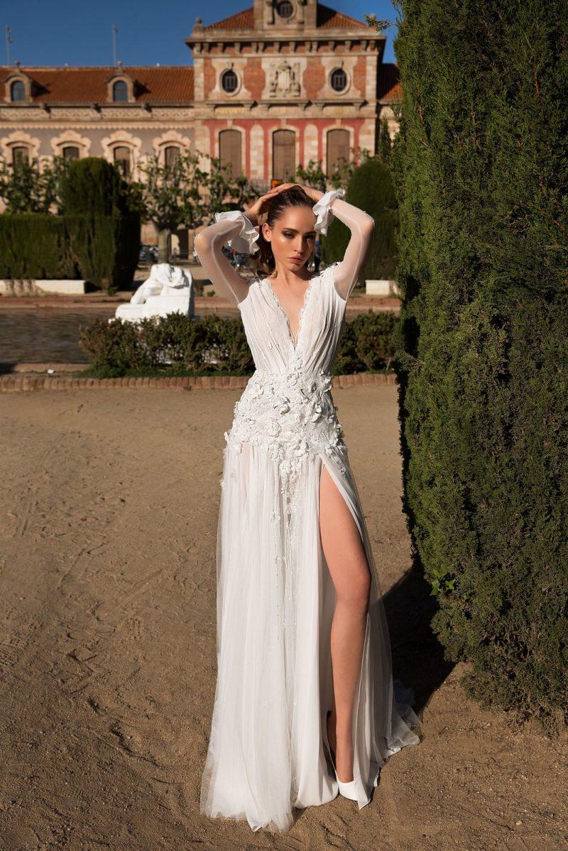 Свадебное платье с соблазнительным вырезом и длинным прозрачным рукавом.