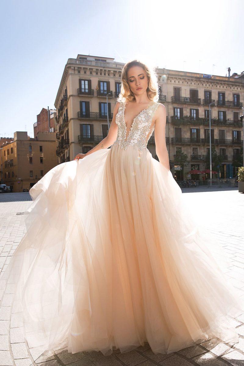 Свадебное платье прямого кроя с глубоким декольте и легкой полупрозрачной юбкой.