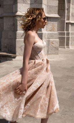 Свадебное платье бежевого цвета, с юбкой миди и белой кружевной отделкой.