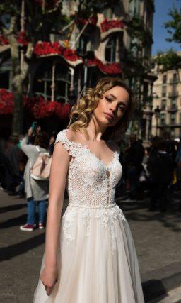 Свадебное платье прямого кроя с кружевной отделкой верха и открытой спинкой.