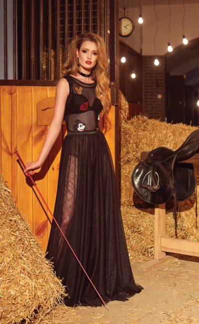 Черное вечернее платье из полупрозрачной ткани, украшенное цветными аппликациями.