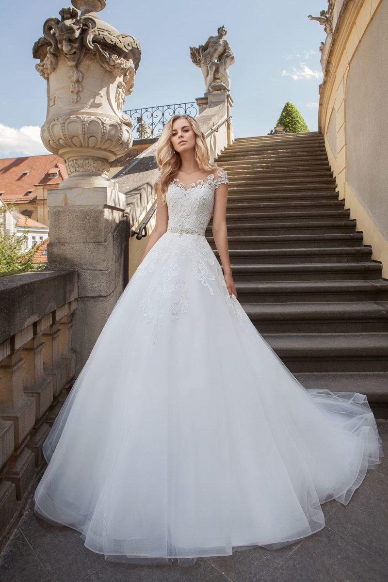 Свадебное платье с фактурным кружевным декором и многослойным низом.