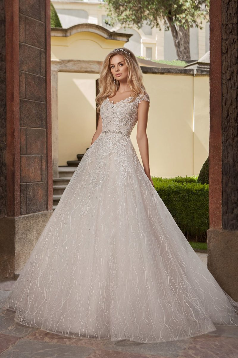 Свадебное платье А-силуэта цвета слоновой кости, с кружевным декором и поясом.
