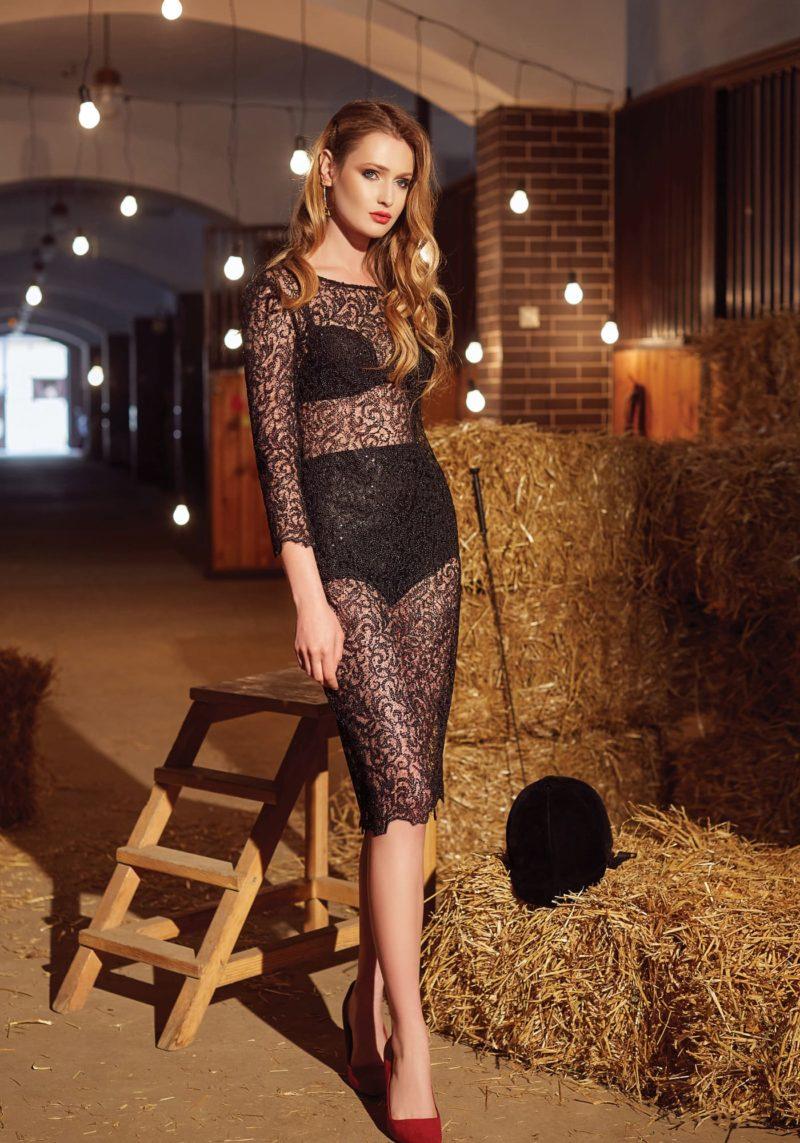 Вечернее платье из черного кружева, с рукавом три четверти и юбкой до колена.