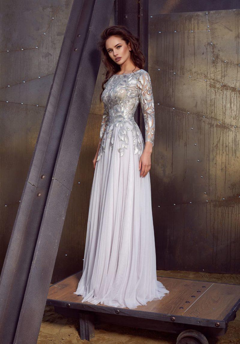 Белое вечернее платье с серебристым декором и закрытым верхом с рукавом.