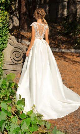 Глянцевое свадебное платье с коротким кружевным рукавом и открытой спинкой.