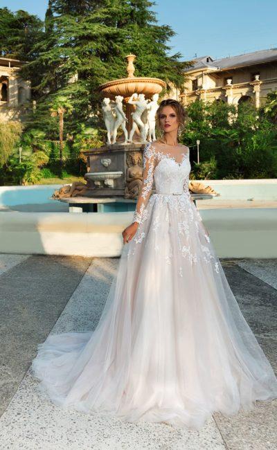 Свадебное платье с длинным полупрозрачным рукавом и роскошной юбкой со шлейфом.