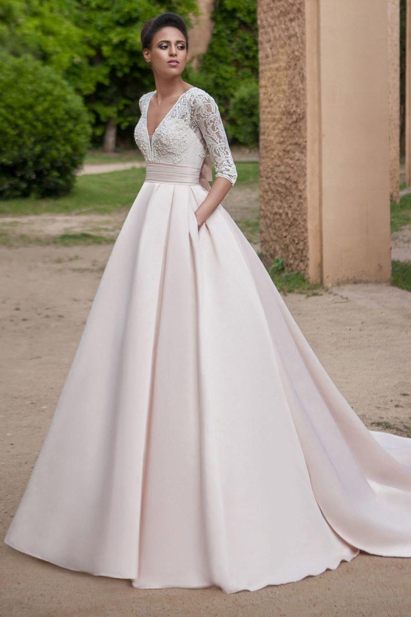Роскошное свадебное платье с кружевным рукавом и розовой юбкой.
