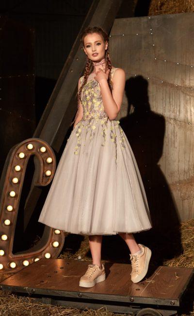 Вечернее платье песочного цвета с желтой отделкой и стильным вырезом на спинке.