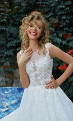 Пышное свадебное платье с полупрозрачным верхом и многослойной юбкой.