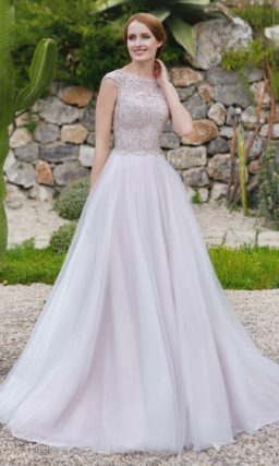 Свадебное платье с закрытым кружевным верхом и многослойной юбкой А-силуэта.