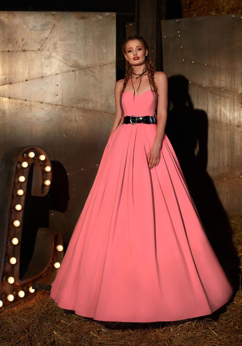 Вечернее платье розового цвета с открытым лифом и эффектным черным поясом.