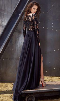 Вечернее платье темно-синего цвета со смелым разрезом на юбке и длинным рукавом.