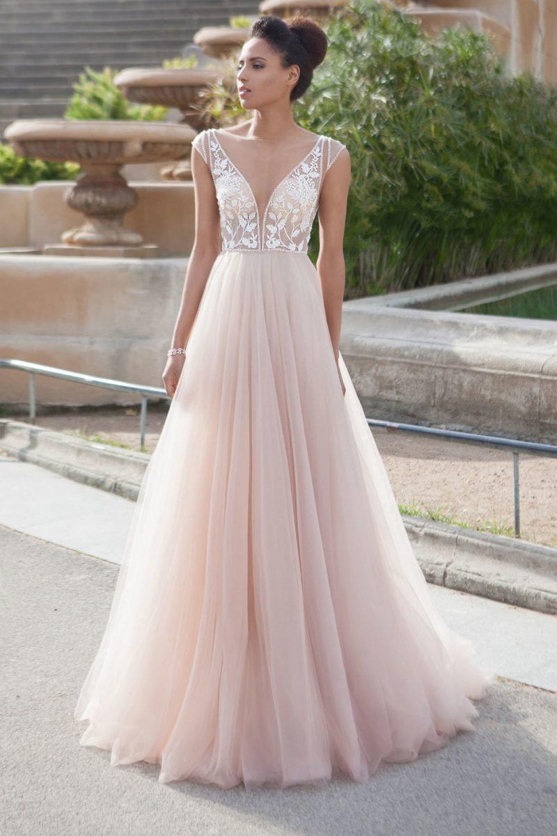 Пудровое свадебное платье с глубоким вырезом декольте и изящным оформлением спинки.
