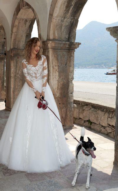 Свадебное платье пышного кроя с крупными кружевными аппликациями и длинным рукавом.