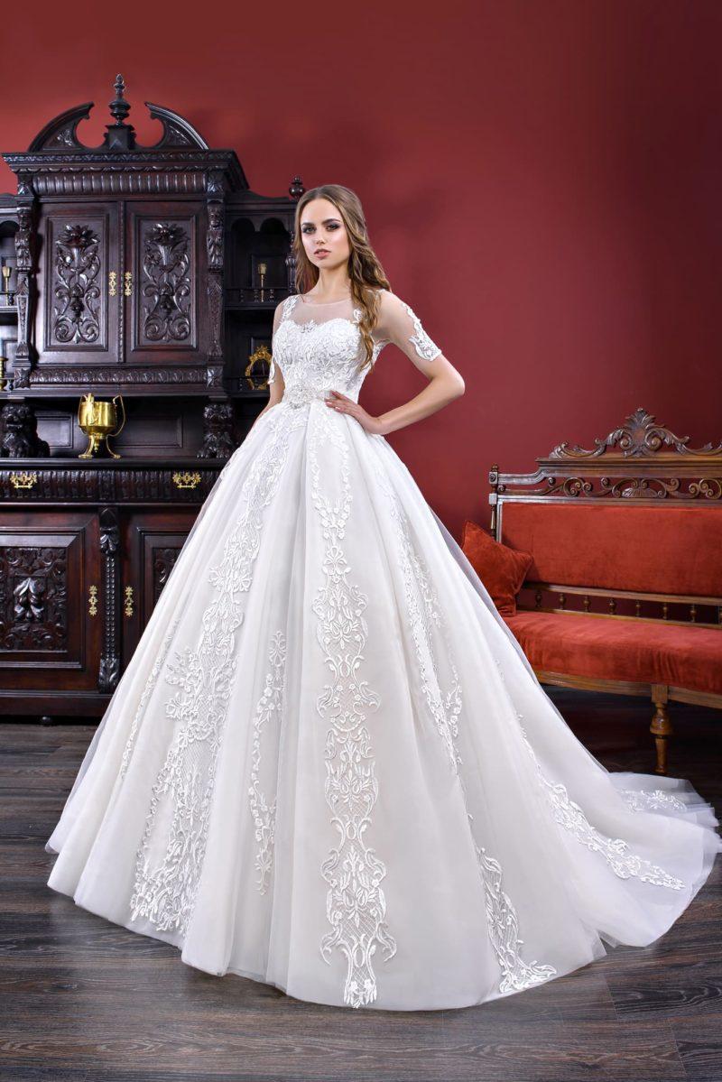 Пышное свадебное платье с полупрозрачным рукавом до локтя и кружевной отделкой.