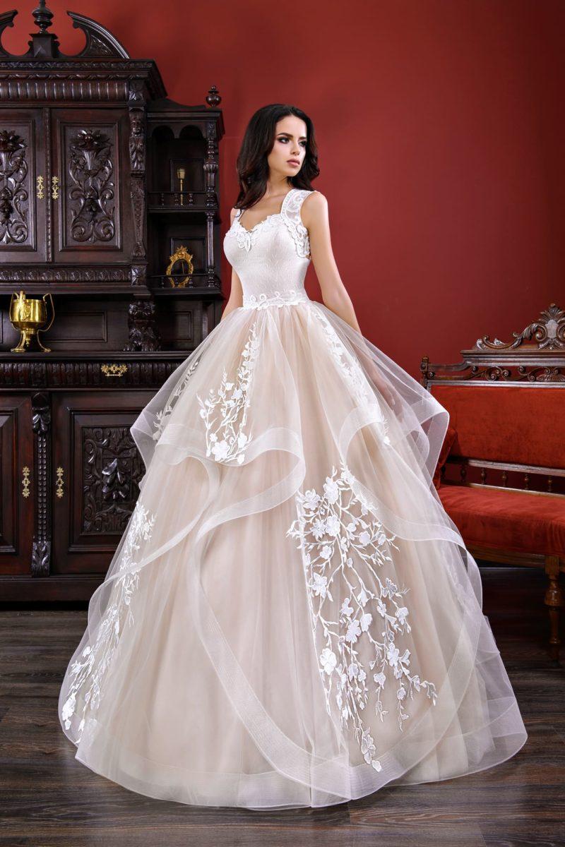 Пудровое свадебное платье с многослойной юбкой и широкими бретельками на плечах.